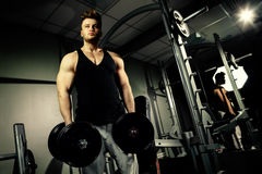 Strong bodybuilder athlete with heavy  dumbbells in gym Stock Photo