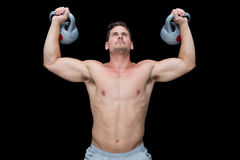 Strong bodybuilder lifting up kettlebells Stock Photo
