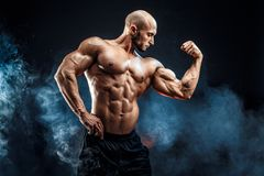 Strong bodybuilder man with perfect abs, shoulders,biceps, triceps, chest. Strong bald bodybuilder with six pack. Bodybuilder man with perfect abs, shoulders royalty free stock photo