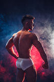 Strong bodybuilder. Man with perfect abs, shoulders,biceps, triceps and chest, personal fitness trainer flexing his. Muscles in blue, red smoke. Back view Stock Images