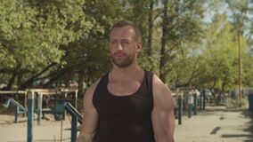 Strong bodybuilder performing barbell biceps curls. Portrait of concentrated handsome bodybuilder performing barbell biceps curls while working out at outdoor stock video footage