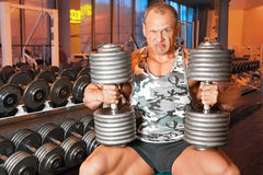 Strong bodybuilder training muscles in gym Stock Images