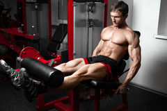Strong bodybuilder training quads. In the gym royalty free stock photography