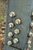 STRONG BOLTS ON STRUT OF ELECTRICAL PYLON. Large metal bolts and screws fastenings on support of robust electrical pylon stock photos