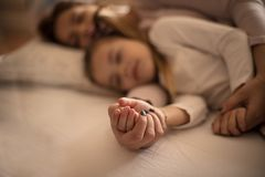 Strong bonding. Mother and daughter sleeping together royalty free stock photography