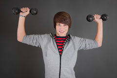 Strong boy with dumbbells. Strong young boy with dumbbells royalty free stock photos