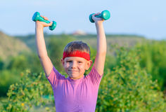 Strong Boy Lifting Two Small Dumbbells Royalty Free Stock Photography
