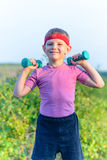 Strong Boy Lifting Two Small Dumbbells Stock Photography