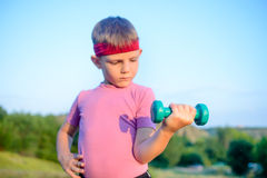 Strong Boy in an Outdoor Exercise Lifting Dumbbell Royalty Free Stock Photos
