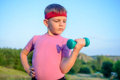 Strong Boy in an Outdoor Exercise Lifting Dumbbell Royalty Free Stock Images