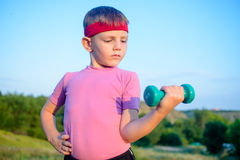 Strong Boy in an Outdoor Exercise Lifting Dumbbell Royalty Free Stock Image