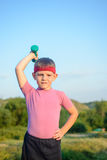 Strong Boy Raising Dumbbell with One Hand on Waist Royalty Free Stock Photos