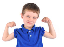 Strong Boy with Tough Muscle. A young boy has his muscles showing in a blue t-shirt. He has a tough smile and there is a white background. Use it for a strength Royalty Free Stock Images