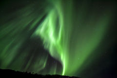 Strong bright green aurora northern lights over mountain Stock Photos