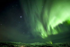 Strong bright green aurora northern lights over mountain Royalty Free Stock Image