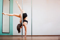 Strong brunette pole dancing Stock Photo
