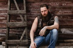 Strong brutal man with a beard and tattoos on his hands dressed in leather vest and jeans sits on a wooden wall royalty free stock photography