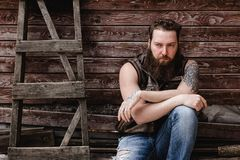 Strong brutal man with a beard and tattoos on his hands dressed in leather vest and jeans sits on a wooden wall royalty free stock image