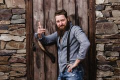 Strong brutal man with a beard and tattoos on his hands dressed in stylish casual clothes poses on the background of stock photos