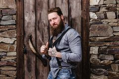Strong brutal man with a beard and tattoos on his hands dressed in stylish casual clothes poses on the background of stock images