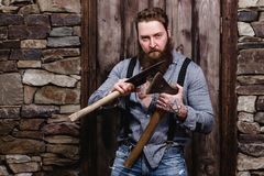 Strong brutal man with a beard and tattoos on his hands dressed in stylish casual clothes stands with two axes in his stock photo