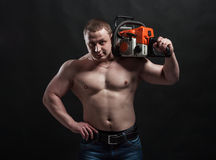 Strong brutal man. With chainsaw on his shoulder royalty free stock image
