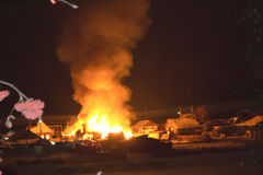 Strong burning house at night in the village. royalty free stock photo