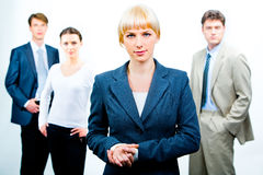 Strong business leader. Portrait of serious businesswoman wearing suit on the background of three confident businesspeople Stock Images