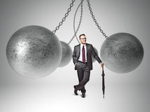 Strong businessman. 3d image of huge swinging metal ball and businessman Stock Photos