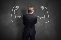 Strong businessman. In front of a blackboard royalty free stock photography