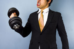Strong businessman. Strong multiracial businessman lifting dumbbell Royalty Free Stock Image