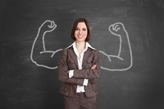 Strong businesswoman is standing in front of blackboard stock image