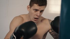 Strong caucasian man boxing using punch sake. Free fighter with tattoo training punching bag, close up stock video