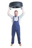 Strong cheerful engineer holding tire above head Royalty Free Stock Photography