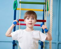 Strong child boy exercising with dumbbells Stock Photos