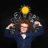 Strong child boy with lightbulb on blackboard background. Brainstorming and idea concept.  royalty free stock photography