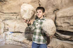 Strong child holds heavy stone Royalty Free Stock Images