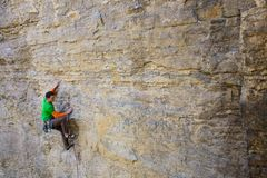Climber climbs the rock. A strong climber in the green shirt climbs on the rock. extreme sports in nature Royalty Free Stock Photo