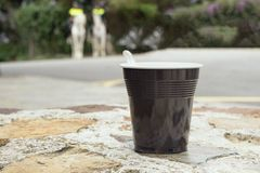 Strong coffee in a brown plastic cup on a stone bench. Coffee break while traveling stock photo