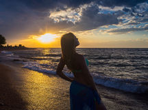 Strong confidence woman open arms under the  sunrise at seaside. Strong confidence woman open arms under the sunrise at seaside Royalty Free Stock Photography