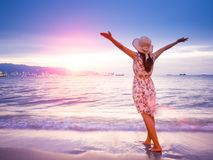 Strong confidence woman open arms under the sunrise at seaside. Summer and travel concept royalty free stock photo
