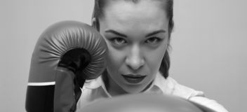 Strong and confident businesswoman wearing blouse and boxing gloves stock photo