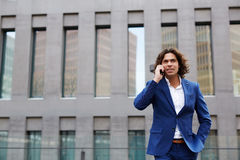 Strong confident man in a stylish suit road talking on the phone royalty free stock photos