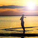 A strong confident woman open arms to sunset. A strong confident women open arms to sunset. On the beach stock photos
