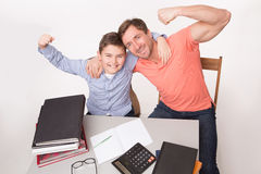 Strong and corageous father and son sitting at table Stock Image