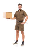 Strong courier. Happy messenger standing and holding big package on one hand. Full length studio shot isolated on white Stock Photo
