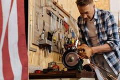Strong crafty mechanic using grinding machine Royalty Free Stock Photo