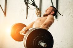 Man lifting weights. muscular man workout in gym doing exercises with barbell. Strong cross fit athlete in the middle a heavy snatch lift in a cross-fit box gym Royalty Free Stock Images