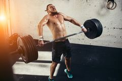 Man lifting weights. muscular man workout in gym doing exercises with barbell. Strong cross fit athlete in the middle a heavy snatch lift in a cross-fit box gym Stock Photo