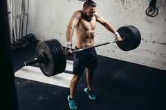 Man lifting weights. muscular man workout in gym doing exercises with barbell. Strong crossfit athlete in the middle a heavy snatch lift in a cross-fit box gym Stock Images
